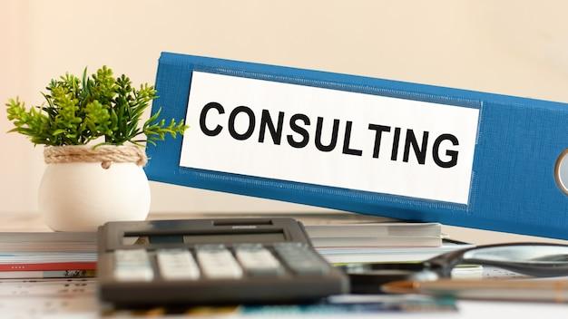Consulting - blauwe binder op bureau op kantoor met rekenmachine, pen en groene potplant. kan worden gebruikt voor zakelijk, financieel, onderwijs, audit en belastingconcept. selectieve aandacht.