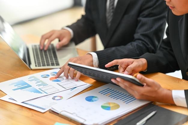 Consulting business met two-man analyse financieren data met apparaat en papieren document.