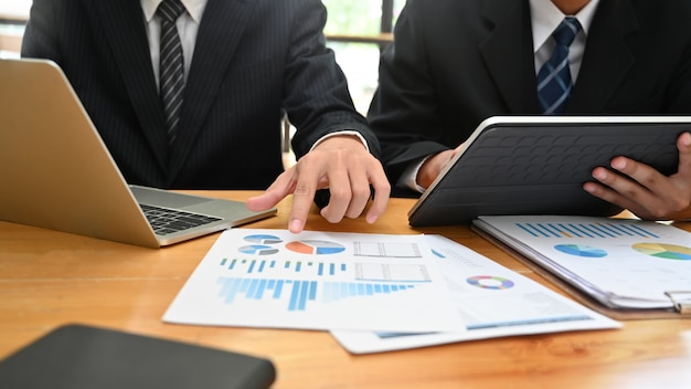 Consulting business met two-man analyse financieren data met apparaat en papieren document.