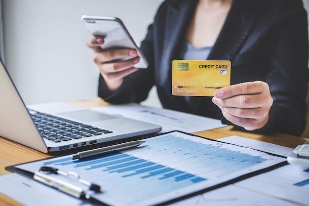 Consumentenholding smartphone, creditcard en typen op laptop voor online winkelen en betalen