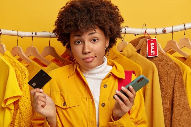 Consumentisme, winkelen en levensstijlconcept. onbewust clueless vrouw met krullend haar houdt creditcard en mobiele telefoon vast