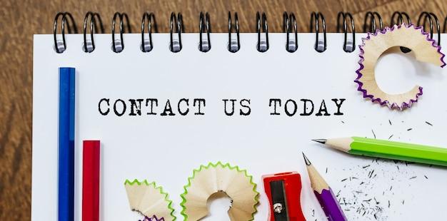Contacteer ons vandaag tekst geschreven op papier met potloden in kantoor
