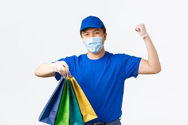 Contactloos betalen, covid-19, virus- en winkelconcept voorkomen. vrolijke aziatische bezorger met medisch masker en handschoenen aan het werk tijdens pandemie, winkeltassen overhandigen met bestelling van de klant.