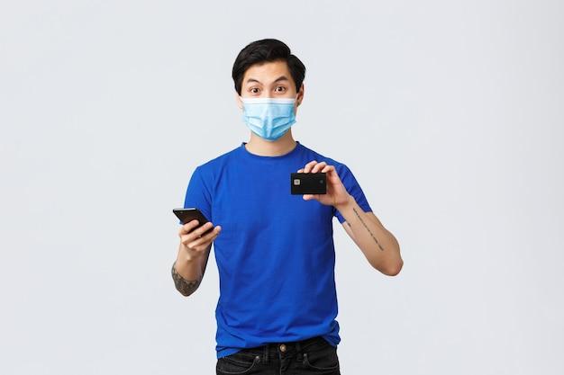 Contactloos betalen, online winkelen tijdens covid-19 en pandemisch concept. enthousiaste jongeman die nieuwe bankfunctie probeert, applicatie op smartphone downloadt, creditcard toont