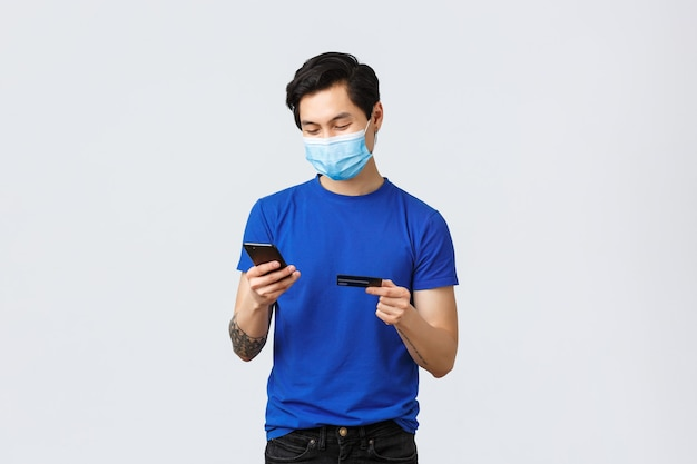 Contactloos betalen, online winkelen tijdens covid-19 en pandemisch concept. jonge zorgeloze man plaatst bestelling, voert creditcardcijfers in om iets op internet te kopen, typt op mobiele telefoon, draagt een masker.