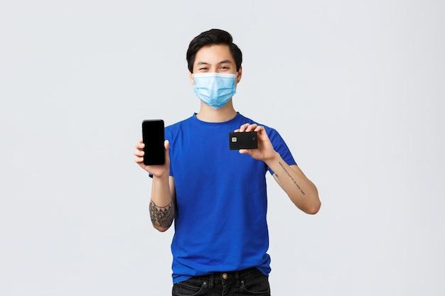 Contactloos betalen, online winkelen tijdens covid-19 en pandemisch concept. knappe jonge glimlachende aziatische man die bestellingen vanuit huis maakt met behulp van mobiele app en creditcard, smartphonescherm toont.