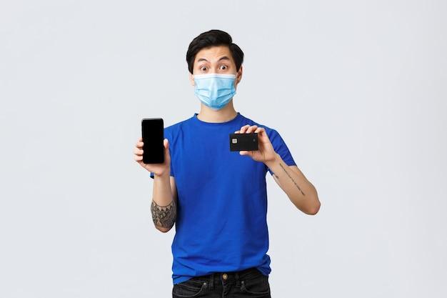 Contactloos betalen, online winkelen tijdens covid-19 en pandemisch concept. verrast jonge aziatische man die je zijn smartphone-applicatie, bankrekening-app en creditcard laat zien