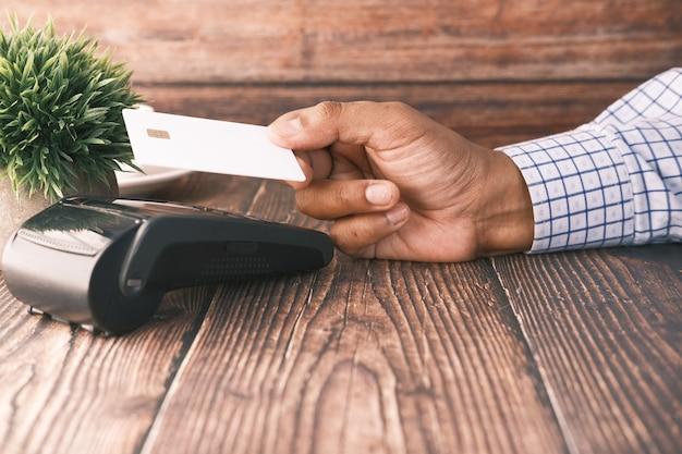 Contactloos betalingsconcept met jonge man die met creditcard betaalt