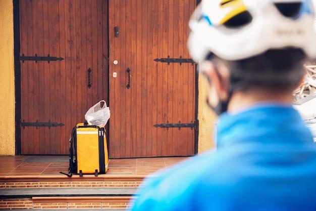 Contactloze bezorgservice tijdens quarantaine. man levert eten en boodschappentassen tijdens isolatie. kloppen aan de deur en goederen achterlaten totdat de klant het ophaalt. veiligheid, ontvangen, afstand houden.