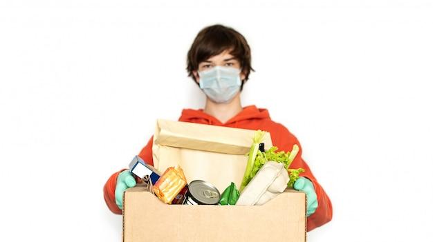 Contactloze levering. een man in een medisch masker en handschoenen houdt een doos. isoleer exemplaarruimte.