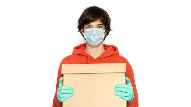 Contactloze levering. een man in een medisch masker en handschoenen houdt een doos. isoleer, kopieer ruimte. coronavirus isolatie online levering van producten en goederen, winkelen