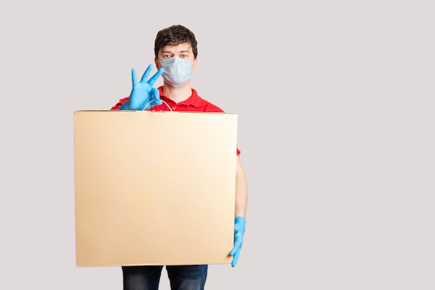 Contactloze levering. mannelijke bezorger in uniform, rubberen handschoenen en een medisch masker houdt een doos. online bestellen tijdens coronavirusquarantaine.