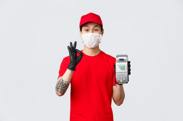 Contactloze levering, veilige aankoop en winkelen tijdens het coronavirusconcept. vriendelijke aziatische koerier in rode uniforme pet en t-shirt, draag medisch masker en handschoenen, toon pos-terminal en goed teken