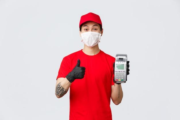 Contactloze levering, veilige aankoop en winkelen tijdens het coronavirusconcept. vrolijke aziatische koerier met medisch masker en handschoenen, met betaalterminal, duim omhoog voor het gebruik van pos-aankoopgoederen.