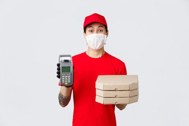 Contactloze levering, veilige aankoop, winkelen tijdens het coronavirusconcept. enthousiaste pizzabezorger met medisch masker en handschoenen, breng bestelling naar klant die met creditcard betaalt met behulp van pos-terminal.