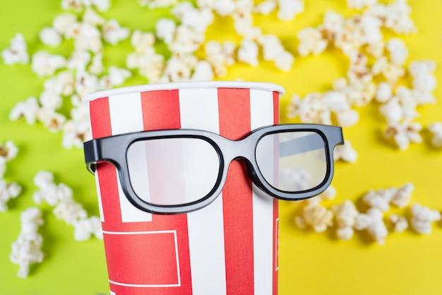 Container in specificaties verspreide popcorn geïsoleerde gele achtergrond