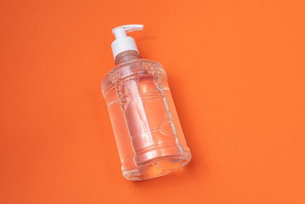 Container met alcohol gel op de oranje muur