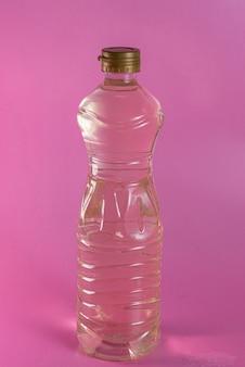 Container met azijn op de roze achtergrond