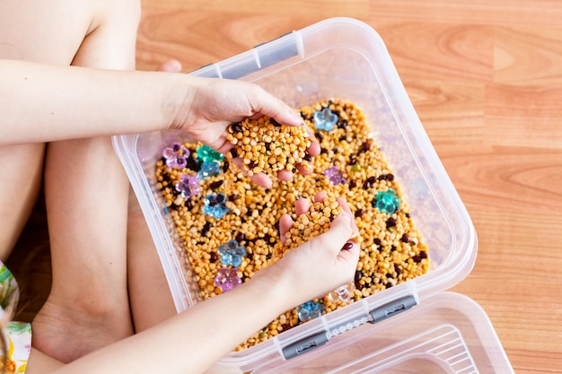 Container met granen, materialen voor de ontwikkeling van kinderen, fijne motoriek, logica en geheugen, geest, meisje ontwikkelt, spelletjes met zand, ontwikkeling van kinderen, jeugd, voorbereiding op school, montessori