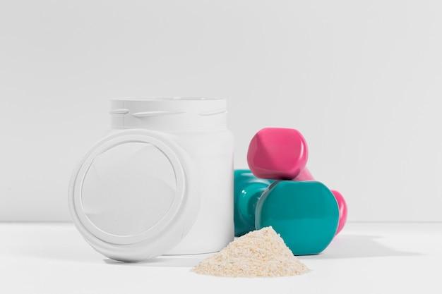 Container met gym supplementen met gewichten