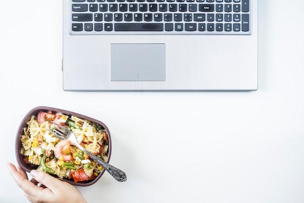 Container met salade met pasta op de werkplek in de buurt van de computer