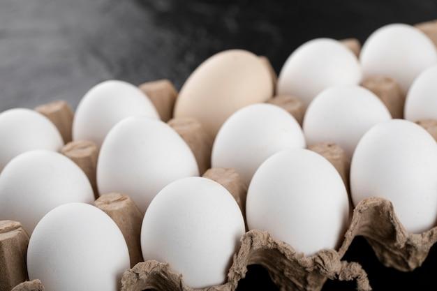 Container met witte eieren op zwarte ondergrond.