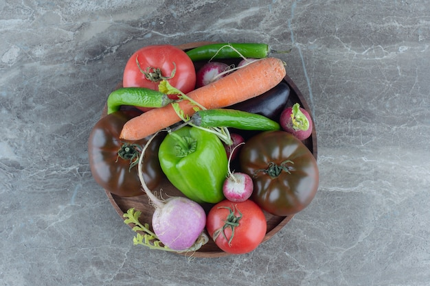 Container vol met gemengde groenten, op de marmeren tafel.