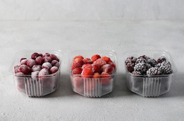 Containers met bevroren bessen: bramen, aardbeien en kersen op het lichtgrijze oppervlak