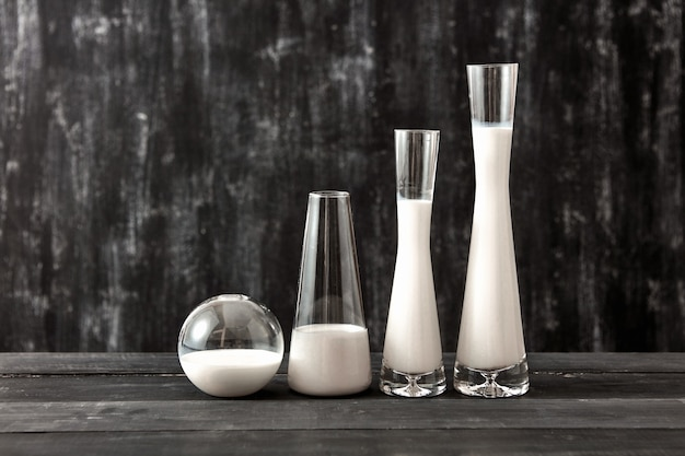 Containers met glazen kegel en bolvorm, gevuld met witte vloeistof