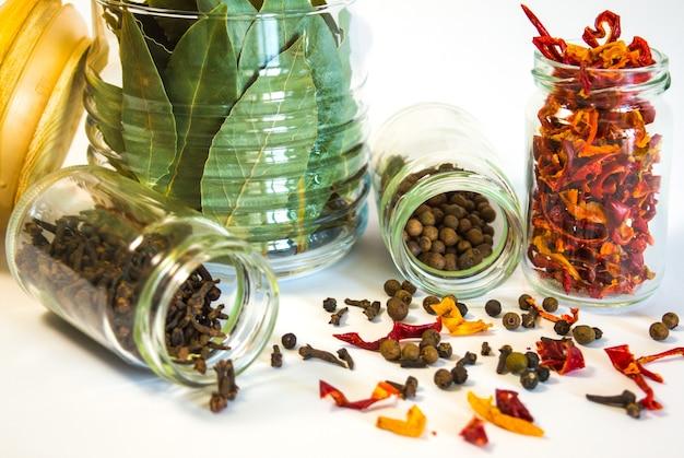 Containers (met glazen potten) met kruiden (laurierblad, kruidnagel, peper, gedroogde paprika) op witte achtergrond. objecten isoleren.