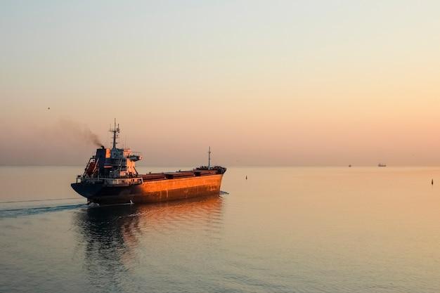 Containerschip aan de horizon, in ochtendstralen