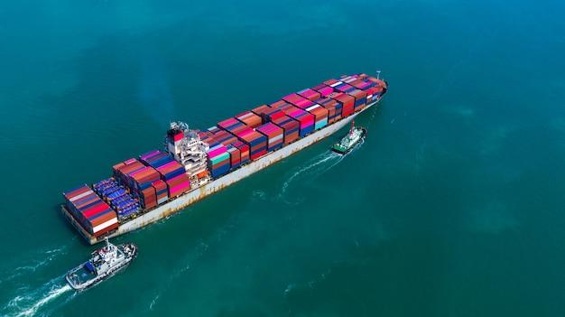 Containerschip die in haven, containerschip en sleepbootboot aankomen die naar diepzeehaven, logistische bedrijfsimport exporteren en vervoer, luchtmening gaan.
