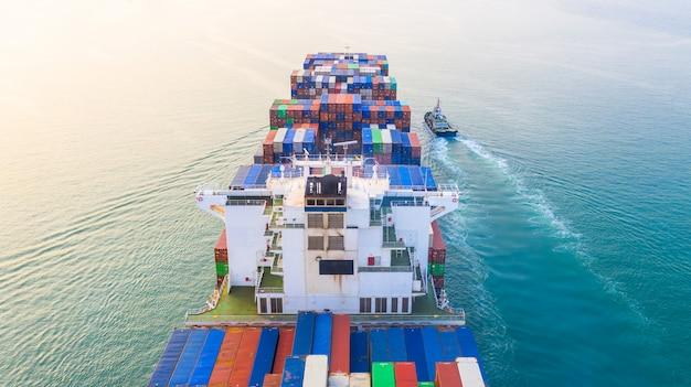 Containerschip die in haven, containerschip en sleepbootboot aankomen die naar zeehaven, logistische bedrijfsimport exporteren en vervoer, luchtmening gaan.