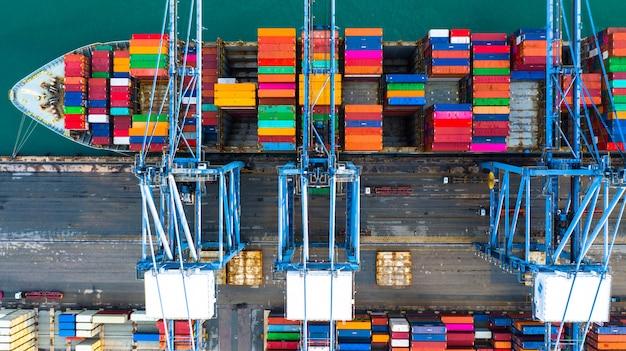 Containerschip dragende containervrachtwagen bij haven voor de invoer en de uitvoer, bedrijfslogistiek en vervoer door containerschip, luchtmening.