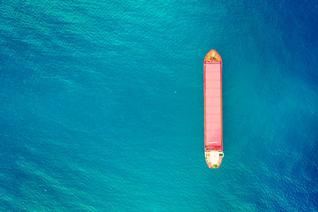 Containerschip in export en import business en logistiek. vracht naar de haven vervoeren. watertransport internationaal. luchtfoto van azuurblauw zeewater en verticaal beeld van rode containerboot. ruimte kopiëren