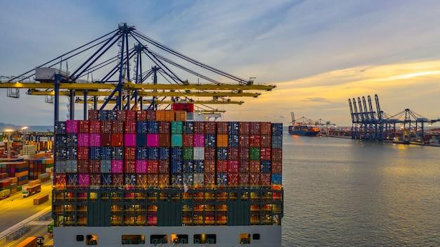 Containerschip laden en lossen in diepzeehaven bij zonsondergang, luchtfoto van zakelijke logistieke import en export