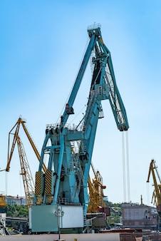 Containervrachtvrachtschip met werkende kraanbrug in scheepswerf overdag.