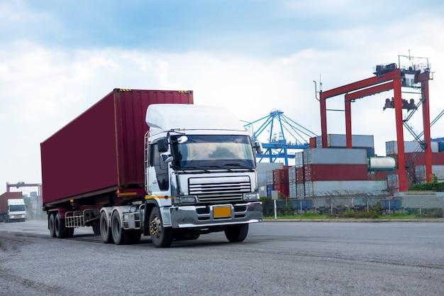 Containervrachtwagen in scheepshaven logistiek. transportindustrie in havenbedrijf. import, export logistiek industrieel