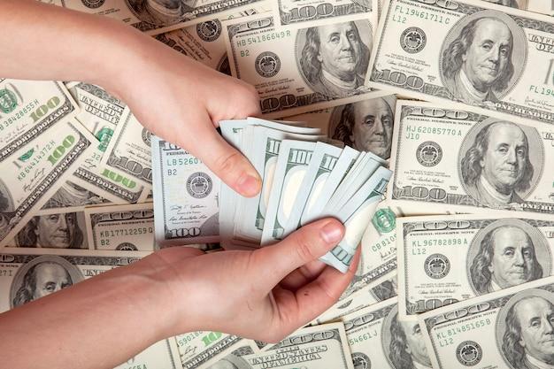Contant geld in de hand. winst, besparingen. stapel dollars. een persoon die geld telt