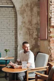 Contemplatieve jonge man met tablet kijkt uit raam zittend in het kleine café van het hotel