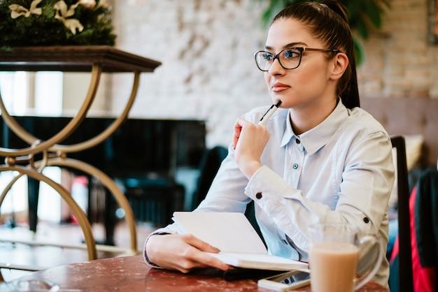 Contemplatieve vrouw die over idee voor project denkt. notities maken in het café.