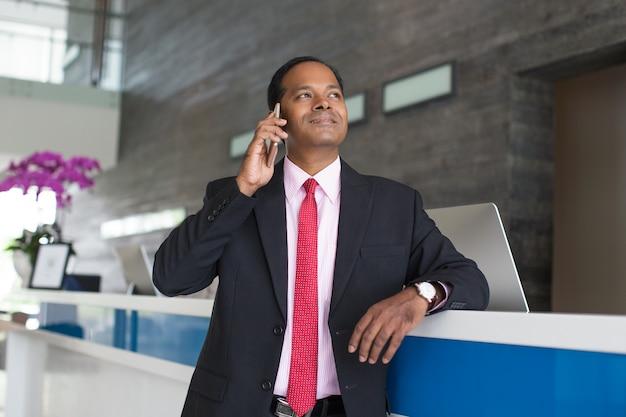 Content business man calling op de telefoon bij de receptie