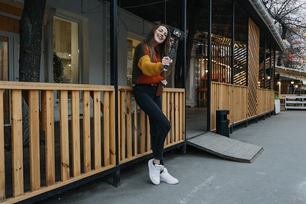 Content creator blogger vlogger jonge vrouw die selfies neemt terwijl ze zichzelf filmt en plezier heeft in de stad