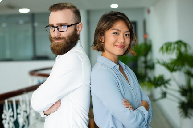 Content jonge multi-etnische collega's staan rug aan rug