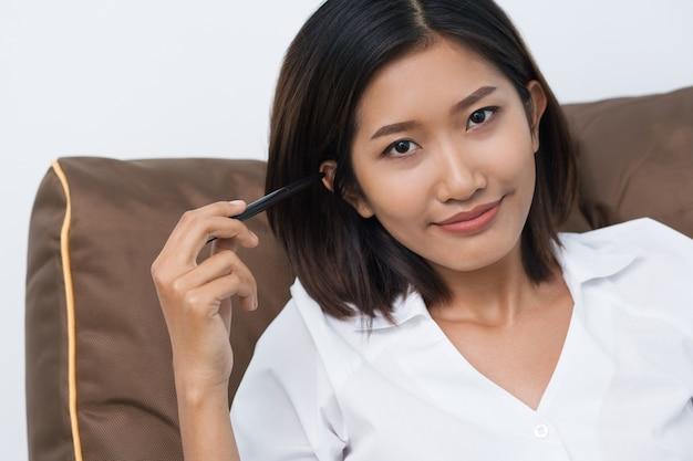 Content vrij aziatische vrouw leunend op kussen