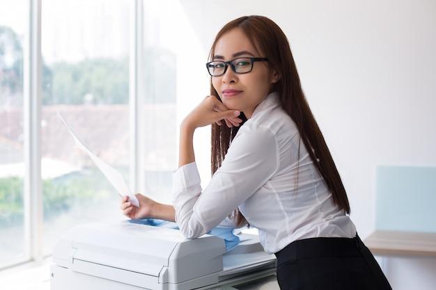 Content vrouwelijke secretaresse met document bij venster