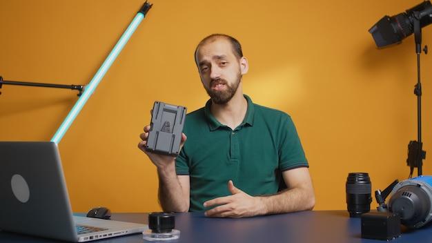 Contentmaker die v-mount batterijbeoordeling voor vlog vasthoudt en opneemt. professionele accumulator. moderne technologie van het v-lock-type, online distributie van sterbeïnvloeders op sociale media