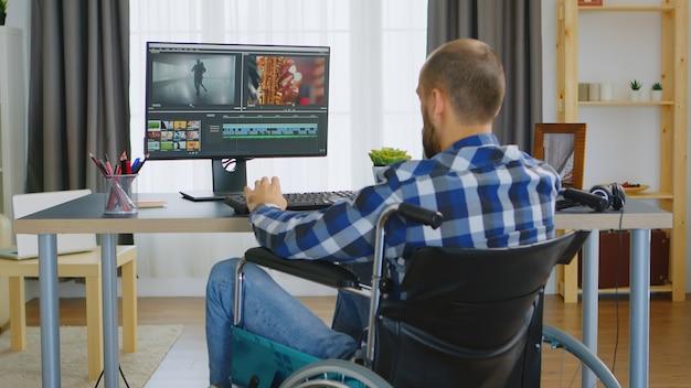 Contentmaker met een loophandicap in een rolstoel die aan een van zijn projecten werkt.