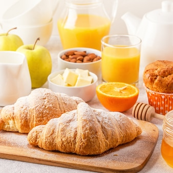 Continentaal ontbijt met verse croissants, jus d'orange en koffie, selectieve focus.