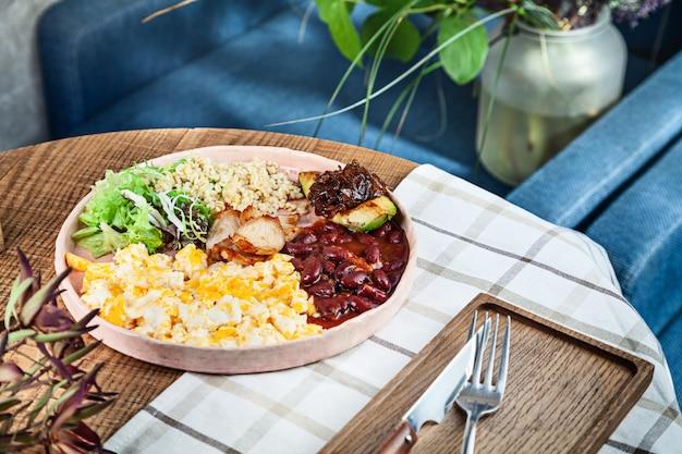 Continentaal ontbijt. modern volledig engels ontbijt met roerei, bulgur, bonen, avocado en sla
